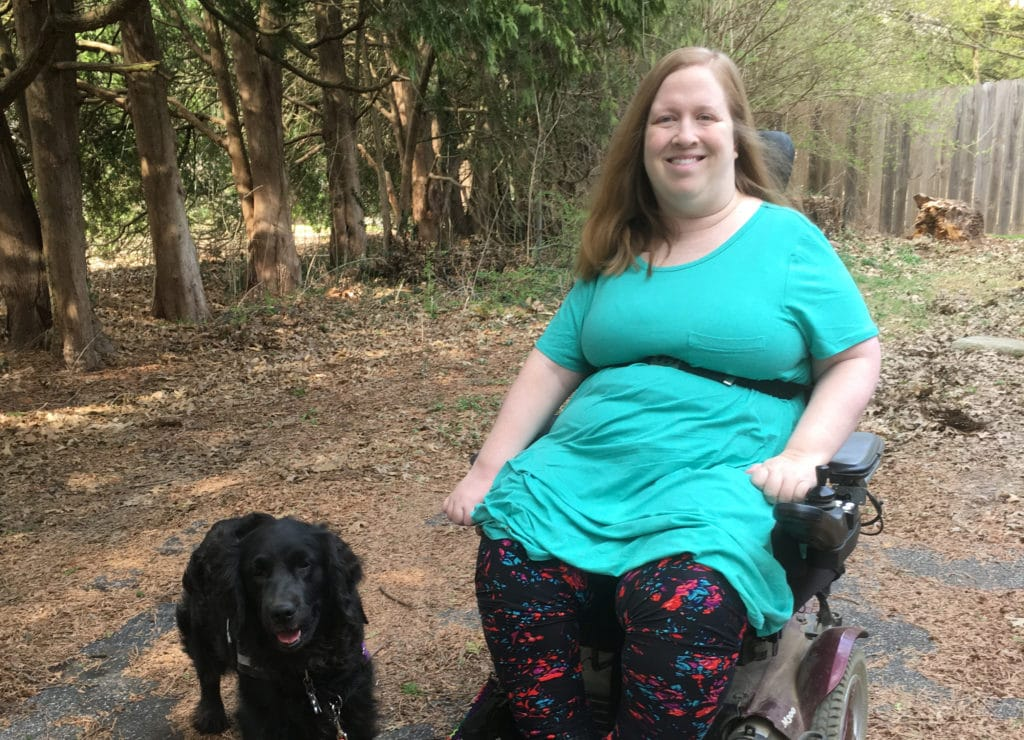 Navigating life when you need home care for a disability during COVID-19. Karin sitting outside in her wheelchair with service dog Aria.