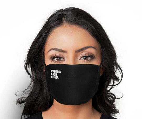 """Latina woman wearing a Sub Zero face mask that says """"Protect Each Other"""" in the corner."""